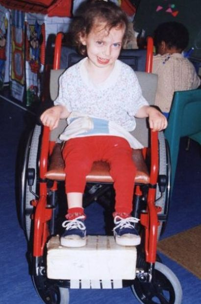Chaeli shows off her first wheelchair, 1997